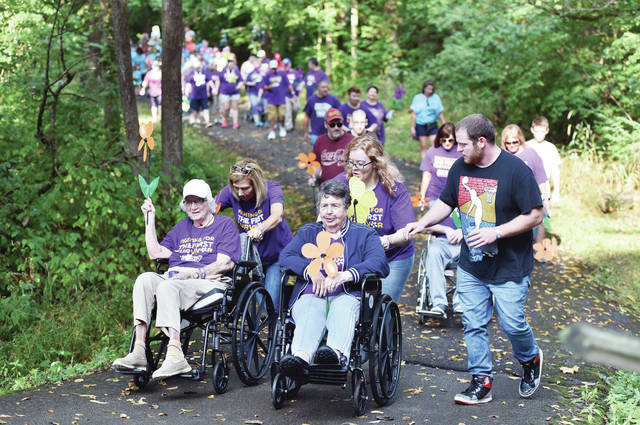 People walk from Flanagan Sports Complex into Tawawa Park during the 2019 Shelby County Walk to End Alzheimer's. This year's walk will be held in local neighborhoods to abide by the COVID-19 social distancing requirements.