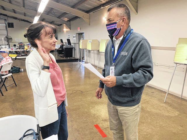 Shelby County Board of Elections Chairman Jim Kerg administers the oath of office to his wife, Theresa Kerg, as an official election observer at Shelby County Fairgrounds Tuesday during the special election.