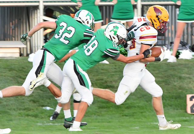 Anna's Trevor Kloeppel tries to drag down New Bremen's Zach Bertke during a Midwest Athletic Conference game on Friday at Booster Field in Anna.