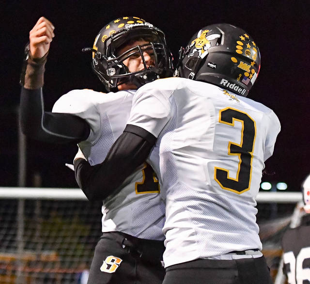 Sidney senior quarterback Cedric Johnson, right, celebrates with Avante Martin after Johnson scored on a 15-yard TD run early in the third quarter of a Miami Valley League game on Friday at Doug Adams Stadium in Xenia. Johnson has thrown for an MVL-best 717 yards and gained 219 rushing yards for the Yellow Jackets.