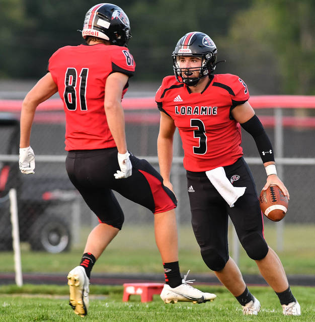 Fort Loramie senior quarterback Collin Moore celebrates with sophomore receiver Logan Eilerman after Moore scored on a 65-yard touchdown run in the first quarter of a Cross County Conference game on Thursday at Smith Field in Covington.