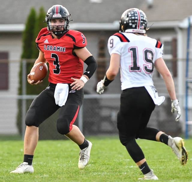 Fort Loramie senior quarterback Collin Moore runs as Covington's Tyler Owens pursues during the first half of a Cross County Conference game on Thursday at Smith Field in Covington.
