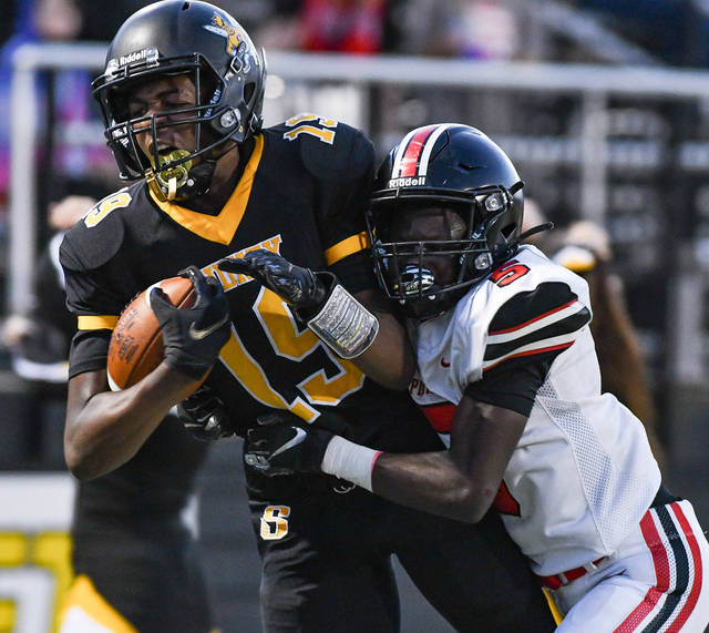 Sidney sophomore receiver Sam Reynolds is tackled by West Carrollton's Cedric Anthony during a 30-yard catch in the second quarter of a Miami Valley League game on Friday at Sidney Memorial Stadium.