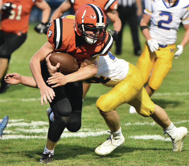 Versailles' Jared DeMange tries to pick up extra yards while being tackled by Marion Local's Darren Meier during a Midwest Athletic Conference game on Friday in Versailles.