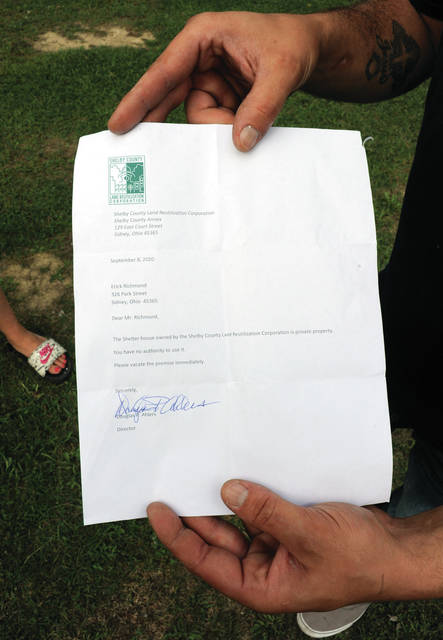 Erick Richmond displays the letter he received from Shelby County Land Reutilization Corporation Director Douglas P. Ahlers telling him to stop feeding homeless people from the shelter house located next to the Alpha Center.