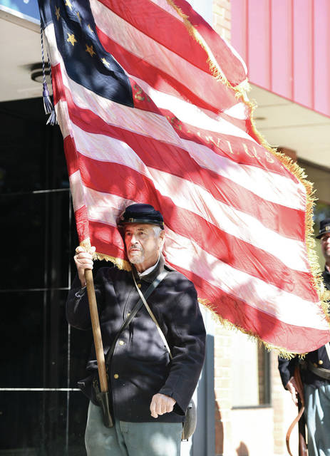 Doug Benson, of Sidney, carries the flag for the 21st Ohio Regiment from Bowling Green during the Sgt. Baker Rededication Ceremony in front of the Monumental Building on Sat., Sept. 19.