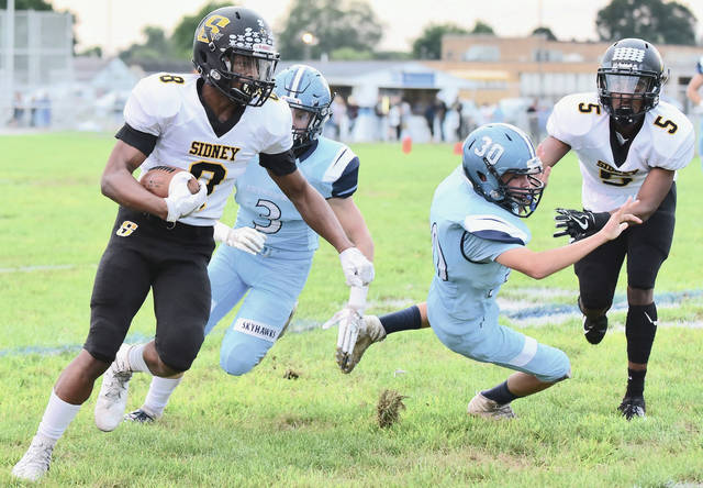 Sidney's Ratez Roberts runs as Josiah Hudgins helps clear his path during a Greater Western Ohio Conference game against Fairborn on Sept. 21, 2018 at Buschemeyer Field in Fairborn. The Yellow Jackets were scheduled to travel to Fairborn Week 4, but a COVID-19 outbreak among Skyhawks players has forced the game to be canceled. Sidney will travel to Xenia on Sept. 18 instead.