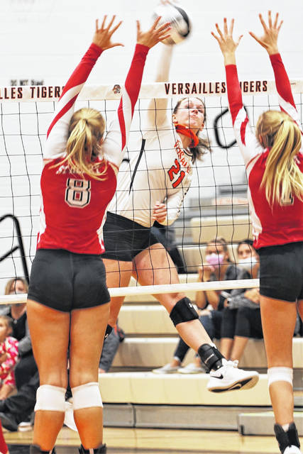 Versailles senior middle hitter Emma George spikes during a Midwest Athletic Conference match against St. Henry on Tuesday in Versailles. George has made a team-high 123 kills this season.