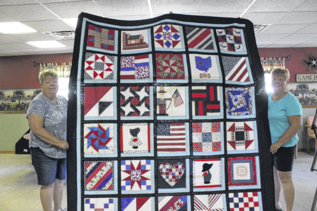 Marilyn Monnin, left, and her twin sister Wanda Monnin, hold up a hand-made quilt they and their friends made for a raffle. All proceeds from the raffle will be donated to the Shelby County Right to Life as well as Rustic Hope.