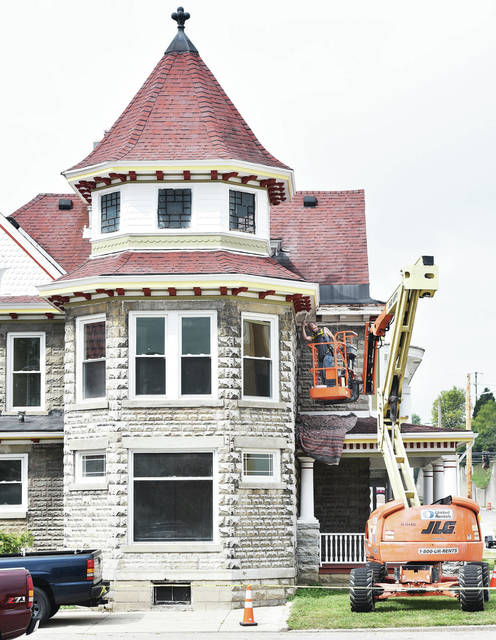 "Thomas Wolfe, of Troy, paints a building at 215 W. Court St., on Tuesday, Sept. 1. The building is zoned commercial and is currently unoccupied as it continues to be refurbished. According to the Shelby County Historical Society the building is registered in the Ohio Historic Inventory and was built in 1876 as a Queen Anne style home. It was the laboratory of Dr. B.S. Hunt, who owned the American Chemical Company which produced a popular ""New Corn Cure"" elixir around 1900. The property also has an adjacent carriage house."