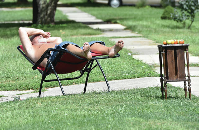 Gary Roesser, of Sidney, catches some rays on his front lawn along East Avenue on Thursday, Sept. 3. Sitting on a stand next to him are tomatoes his wife, Debbie Roesser, grows and puts out for anyone who wants them, free of charge. Roesser grows a variety of other foods such as jalapenos, chili peppers and rhubarb. Roesser doesn't like to be pent-up in his house for too long if he can help it.