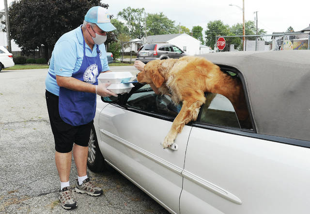 Sidney Kiwanis Club member John Coffield, left to right, hands some chicken bar-b-que meals to Jane Seving, of Sidney, as Seving's dog Charlie rides in the back seat. Coffield was helping with the Kiwanis Club of Sidney Annual Labor Day Chicken Bar-B-Que at the Shelby County Fairgrounds on Monday, Sept. 7. The club sold out of its 2,000 chicken dinners by 3:30 p.m.