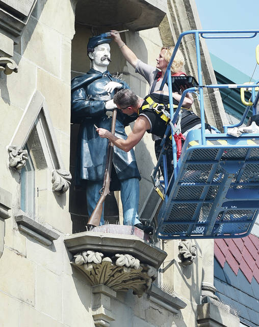 Gallery 2 Ten owner Mila Hamilton, top, of Sidney, adds some fresh blue paint to the hat of SGT. Baker as Ron Wolfe, of Kiser Lake, adds some new brown paint to SGT. Baker's rifle on Wednesday, Sept. 9. The SGT. Baker statue is located at the top of the Monumental Building.