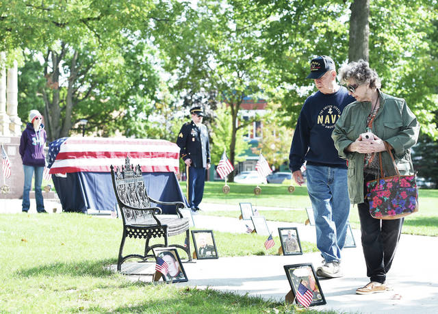 Jessica and retired Army James Vonderhuevel, left to right, both of Sidney, stand watch over a flag draped coffin as U.S. Navy Vietnam Veteran Al and Ann Gurowski, of Morgantown, N.C., look at pictures of U.S. veterans and active duty soldiers who committed suicide. The display was part of the Silent Watch Veteran Suicide Awareness setup by Shelby County Veteran Services on the courtsquare on Tuesday, Sept. 22. The display is an attempt to inform veterans and those that know veterans that there are resources available for veterans dealing with depression. Veterans can call the crisis line 800-273-8255. For benefits local veterans can call 937-498-7282.