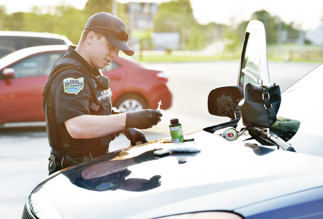 A Sidney Police Officer picks up a syringe and other drug paraphernalia found in a vehicle parked in the Love's parking lot around 6:15 p.m. on Tuesday, Sept. 22. Police were called to Love's on a report of suspected theft. A powder, the Sidney Police believe could be fentanyl, was also found.