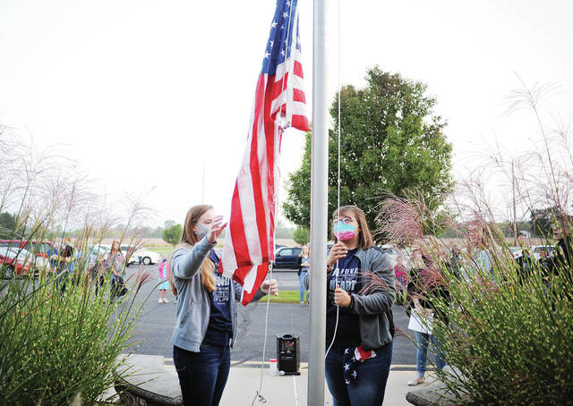 """Christian Academy Schools' students Faith Lord, left, 15, daughter of Anita Lord and Karli Hiler, 15, both of Anna, daughter of Mike and Mindy Hiler, raise the U.S. flag at the start of a """"See You at the Pole"""" ceremony. The event was held at 7:30 a.m. in front of Christian Academy Schools on Wednesday, Sept. 23. Students prayed for America's leaders, performed the """"Pledge of Allegiance"""" and sang the National Anthem. See You at the Pole is a nationwide event."""