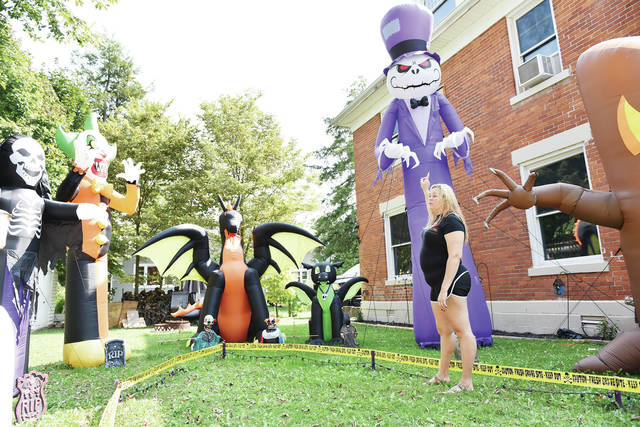"Misty Yokley, of Sidney, gives a tour of her Halloween display outside her house at 528 S Ohio Ave. on Thursday, Sept. 24. The display includes a number of large inflated characters on one side of the house. The porch is filled with animatronic figures and crawling up the right side of the house and peeking into windows are realistic skeletons. Yokley started the display 3-years-ago and said it ""brings joy. Makes me happy. Everybody needs a little bit of enjoyment right now."" Yokley will be handing out candy this year for Halloween."