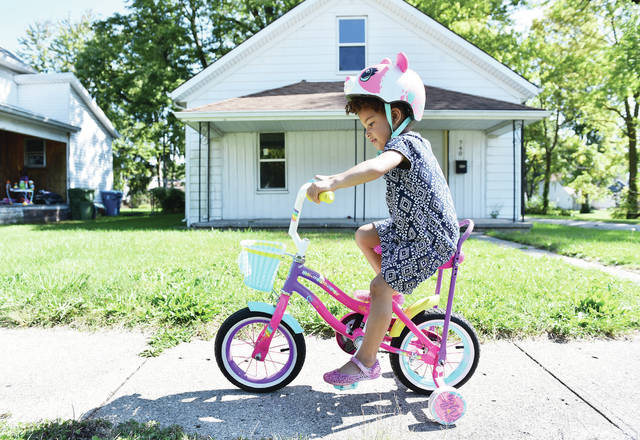 Lyric Fahnestock, 4, of Sidney, daughter of Jacquia Hudgins and Chris Heath, rides her bike along Broadway Avenue on Friday, Sept. 25. Lyric has just started riding again after spending most of the summer sidelined with a broken leg.