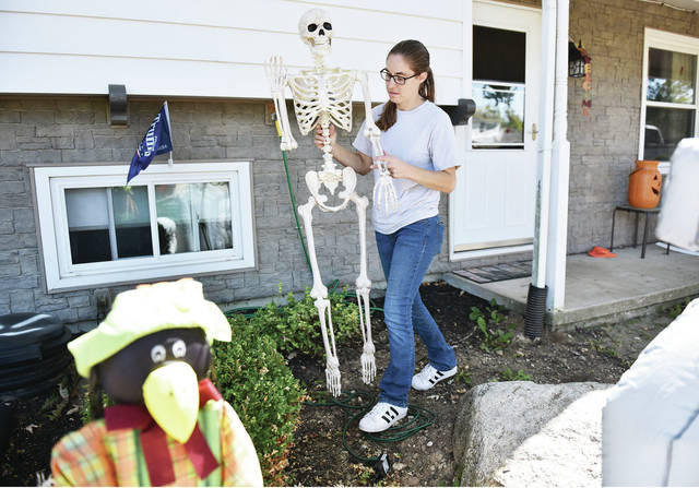 Jessica Suthers, of Sidney, walks a skeleton over to a Halloween display she was helping to setup in front of a house at 2116 Broadway Ave. on Friday, Sept. 25.