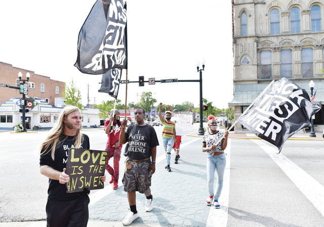 Black Lives Matter protesters held flags and conveyed their message of peace to people interested in learning more about their goals at the intersection of S Ohio Avenue and Court Street on Saturday, Sept. 28. Protests that began at the end of May 2020 were first organized by Wesley Stockton as a reaction to the death of George Floyd while being restrained by police. Stockton and others have continued to be a presence on the courtsquare talking with people about police violence.