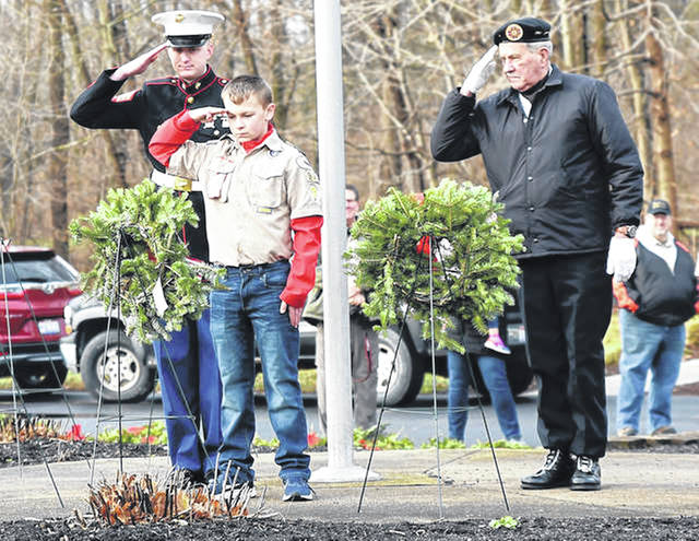 Sgt. Nathan Shultz, USMC recruiter, left to right, Boy Scout Dylan Shaffer, 12, of Houston, and Bill Carpenter, US Marine Corps veteran and member of the Combined VFW-American Legion-AmVets-DAV Honor Guard, lay a wreath at the base of the flag pole at Graceland Cemetery on Saturday, Dec. 14, 2019. The three were taking part in a Wreaths Across America program that the Shelby County Historical Society and the Shelby County Vets to DC teamed up to hold the event. Wreaths were place on the graves of hundreds of U.S. veterans at Graceland Cemetery. Sidney Daily News file photo