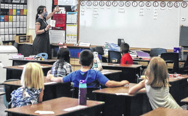 Emerson Primary School first-grade teacher Katie Hall begins the new school year by teaching her students about counting money. Tuesday was the first day of school for Sidney City Schools and Hall's first day of teaching in the district.