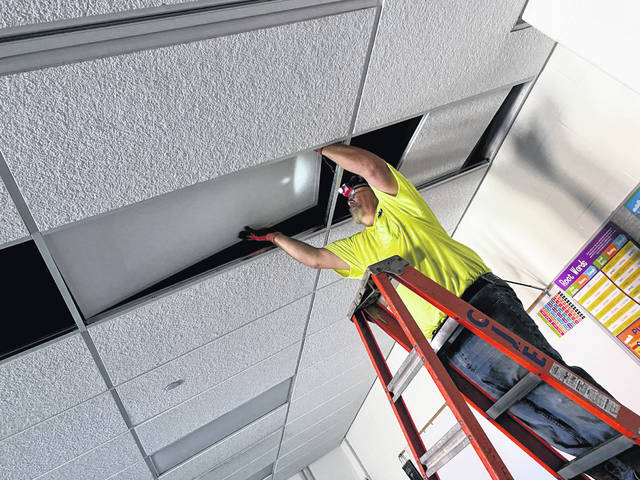 Greg Sharp, with CJ Electric, installs a new light at Sidney Middle School.