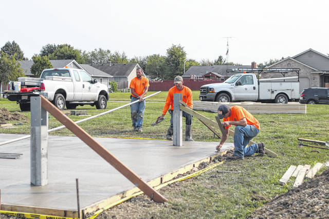 City of Sidney employees Jeremy Dearth, Rodd Elliott and CJ Keener pour the floor for the shelter house at corner of Sherri Ann Avenue and Apache Drive in Sidney where they are building a new park.The goal is to have the playground and shelter house completed by Jan 1.