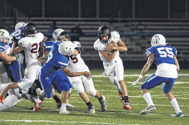 Minster junior quarterback Johhny Nixon carries the ball as Allen East's Jordan Motter tries to close the hole during a Division VI, Region 24 playoff game on Saturday at Allen East.