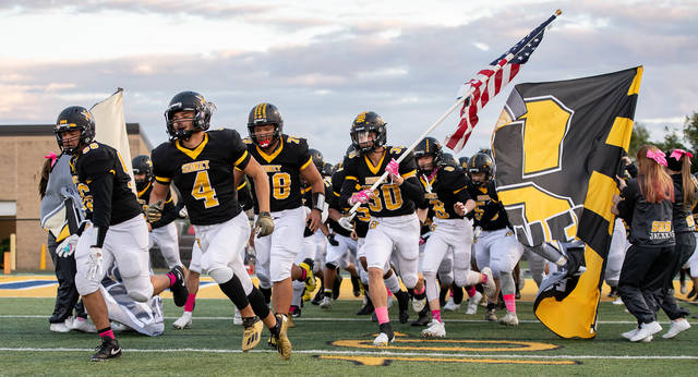 Sidney players run onto the field before a Miami Valley League game against Piqua on Friday at Sidney Memorial Stadium.