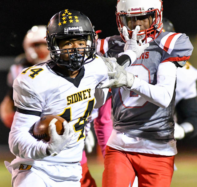 Sidney senior receiver Jacob Wheeler stiff-arms Stebbins' Javin Mack-Brown during the third quarter of a Division II, Region 8 playoff game  on Friday at Edmundson Stadium in Riverside.