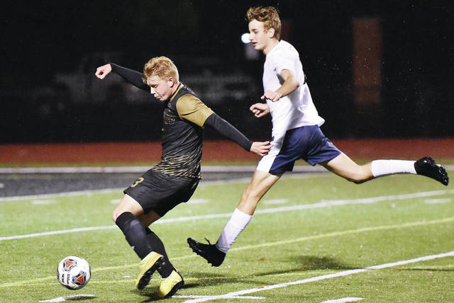 Botkins' Zane Paul takes a shot toward the goal while followed by Xenia Legacy Christian's Andrew Riddle during a Division III district semifinal on Monday at AccuSport Stadium in Bellefontaine.