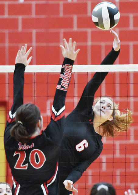 Fort Loramie senior middle hitter Kenzie Hoelscher spikes as Triad's Abby Walls tries to block during a Division IV sectional semifinal on Tuesday at Troy's Trojan Activities Center. Hoelscher, who was named the SCAL player of the year on Thursday, has made 337 kills, 67 total blocks and 43 aces this season.