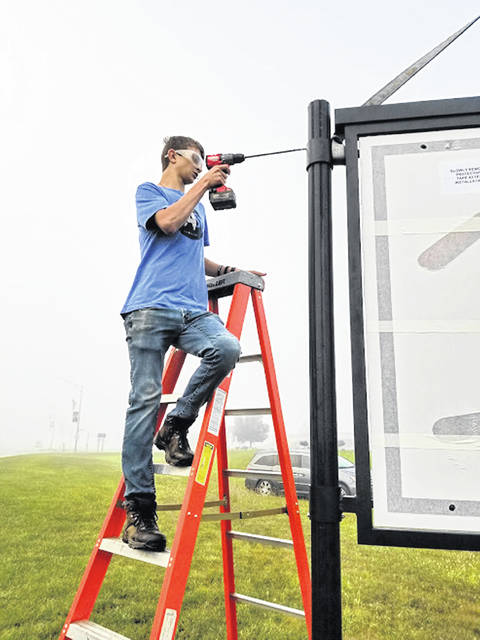 Ethan Huwer, of Minster, works on the new sign at the village's corporation limit. Huwer completed the project for his Eagle Scout award.