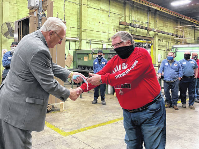 Sidney Mayor Mike Barhorst presents a Sidney Bicentennial lapel pin to Glenn Yount, Sidney Manufacturing's longest tenured employee, during his visit to the company Friday morning during the annual observance of National Manufacturing Day.