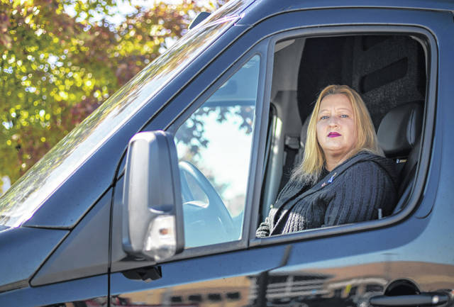 Amy Pache, an undecided voter from Dublin, sits inside her van that she uses in her job as a livery driver on Oct. 13.