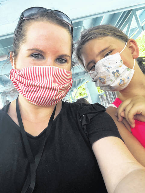 One of Big Brothers Big Sisters matches, Rachel Rains, of Houston, and her little sister, Shelby Hoskins, daughter of Amanda Platfoot, of Minster, wear their masks to stay healthy.