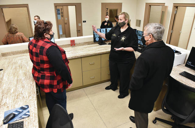 Jail Administrator Sgt. Karla Pleiman, center, talks to Shelby County Common Pleas Court Chief Adult Probation Officer Ruth Cooper, left, and Shelby County Common Pleas Judge James Stevenson about the new intake facility recently built onto the Shelby County Jail during a ribbon cutting ceremony on Friday, Oct. 16. The facility was built to isolate inmates from the rest of the jail until they can be safely checked for any hidden drugs to prevent them from contaminating the rest of the facility with such dangerous drugs such as fentanyl. The intake facility has separate ducts from the rest of the prison so that if a cloud of fentanyl powder were to be sucked up into an air vent it would not spread far. An emergency shut off button also can be used to shut down the air flow in the intake center to limit any drug exposure for other inmates in the intake center's other rooms. The intake center also is being used as a 14 day quarantine for new inmates to make sure they don't potentially infect other inmates with COVID-19. The facility opens on Monday, Oct. 19.