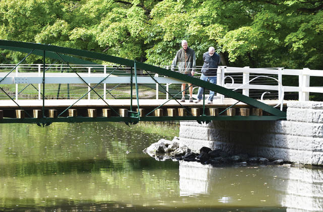 Rick Holly, left, of Sidney, and Keith Dill, of The Villages, Florida, check out the now finished 1879 Zenas King bow string bridge over Amos Lake in Tawawa Park on Friday, Sept. 18. The restored 1879 Zenas King bridge will be officially dedicated at 2:30 p.m. Oct. 17.