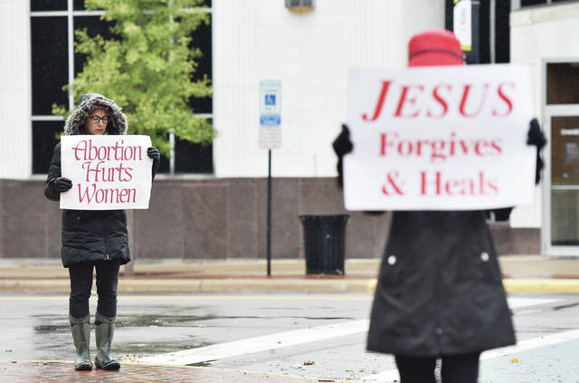 Christina Schmiesing, left, and Dottie Baker, both of Sidney, take part in a National Life Chain event on the courtsquare on Sunday, Oct. 4. Participants prayed to end abortion and held up signs.