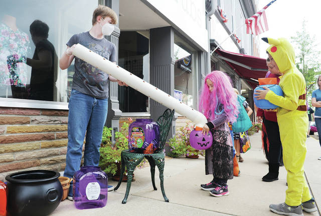 "Ron and Nita's employee Seth Frisby, left, 16, son of Randall and Gwen Frisby, sends candy down a tube and into the bucket of Kaitlyn Wallace, 5, as Kaitlyn's brother Evan Wallace, 7, all of Sidney, watches during trick-or-treating at Ron and Nita's on Saturday, Oct. 10. Kaitlyn was dressed as Audrey from the movie ""Descendants 3."" Audrey and Evan are the children of Alisha and Will Wallace. Also taking part in handing out Halloween candy was the Amos Memorial Library, Gateway Arts Council and the Shelby County Historical Society."