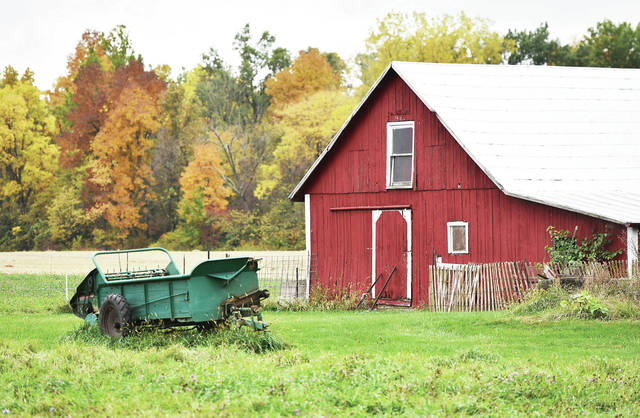 A small barn sits along Hoying Road with a backdrop of trees covered in fall colored leaves. The barn is one of several that were built in 1893 by Charles and Agnes Hoying. The surrounding farmland next to the village of St. Patrick was originally bought from an Irish family before settled on by the German Hoying family. Descendants of Charles and Agnes still own the farm.
