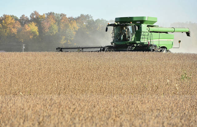 A farmer harvests soybeans with a John Deere combine in a field at the intersection of Redmond Road and and Simon Road on Tuesday, Oct. 13.