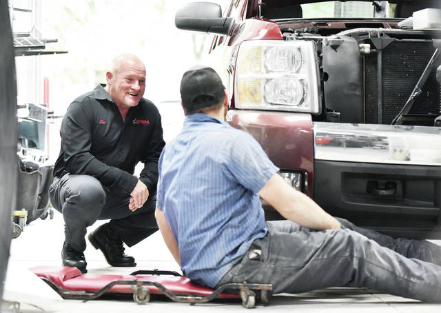 Tom Martin, left, talks with one of his mechanics, Travis Wisman, both of Sidney, at Sidney Body CARSTAR on Wednesday, Oct. 21. BodyShop Business named Martin its executive of the year.