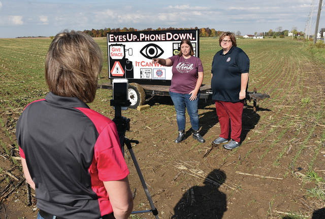 Bambauer Fertilizer and Seed and Shelby County Farm Bureau member Raci Zimpfer, left to right, of Anna, films Leah Fullenkamp, and Shelby County Farm Bureau Director Jill Smith, of Jackson Center, unveiling the new Eyes Up. Phone Down. sign Fullenkamp worked to have made and placed at the intersection of state Route 29 and Fort Loramie Swanders Road on Thursday, Oct. 22. Fullenkamp lost her husband to an inattentive driver.