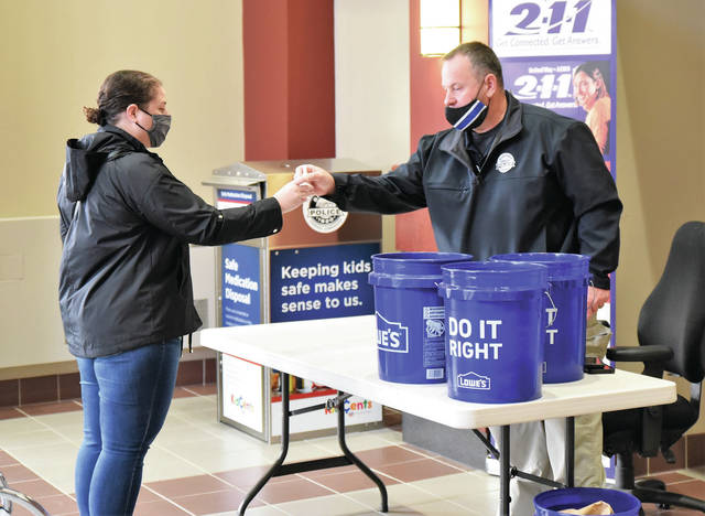 Taylor Sphwarzman, left, of Sidney, turns in expired or unneeded prescription drugs to Sgt. Rob Jameson at the Sidney Police Department Saturday, Oct. 24 morning. The DEA Drug Take Back Program is in itճ 2nd year.