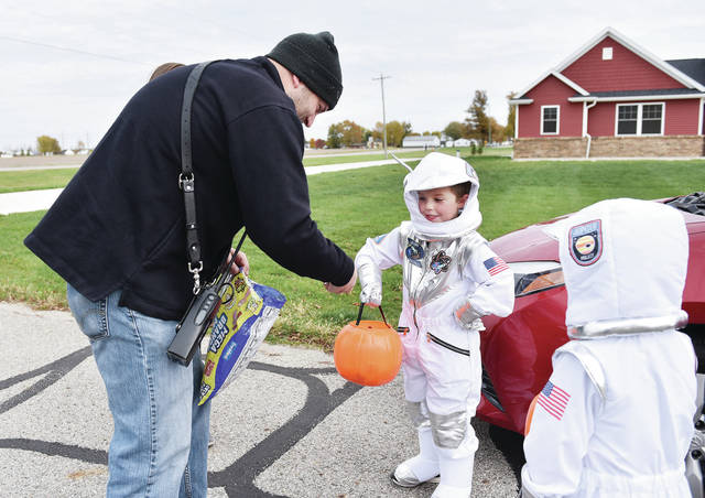 Van Buren TWP firefighter Matt Poppe, left to right, of Kettlersville, hands out candy to Mason Moeller, 7, and Tucker Moeller, 5, both of McCartyville, both children of Kevin and Lisa Moeller, during trick-or-treating in McCartyville on Sunday, Oct. 25.