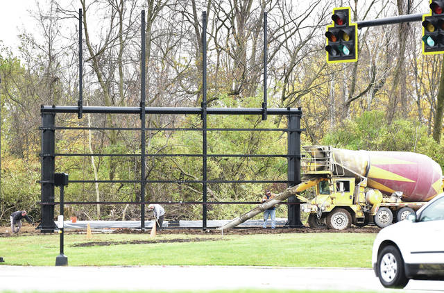 Workers pour concrete onto the base of a frame for what will be a massive digital billboard at the intersection of West Court Street and Fourth Avenue on Wednesday, Oct. 28.