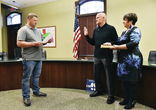 Darrin Goudy, of Highland County, center, is sworn in as the new Anna police chief by Anna Mayor Mark Pulfer, far left. Holding a Bible is Goudy's wife, Molly Goudy. Goudy was sworn in on Friday, Oct. 30.