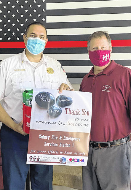 Sidney Fire Department Deputy Chief Chad Hollinger, left, accepts a Week of Appreciation package from Tri-County Board of Recovery & Mental Health Services Director of Community Resource Development Brad Reed.